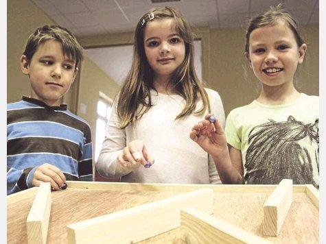 Die Drittklässler sind startklar für ein Experiment zum Rollverhalten der Murmeln auf der aus Holz gefertigten Bahn. Foto: Köller