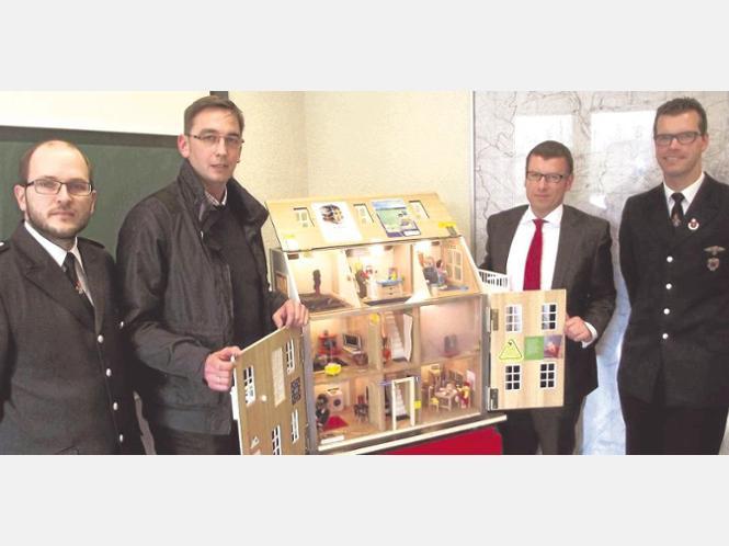 Stefan Czarkowski (2. von links), Leiter der Freiwilligen Feuerwehr Halver, sein Stellvertreter Thorsten Wingenbach (links), Björn Clever (rechts), stellvertretender Stadtjugendfeuerwehrwart und Leiter des Ressorts Kinderbrandschutzerziehung sowie Thorsten Haering, Direktor der Sparkasse Lüdenscheid, mit dem Rauch-Haus, das durch eine Spende des Geldinstituts finanziert wurde.