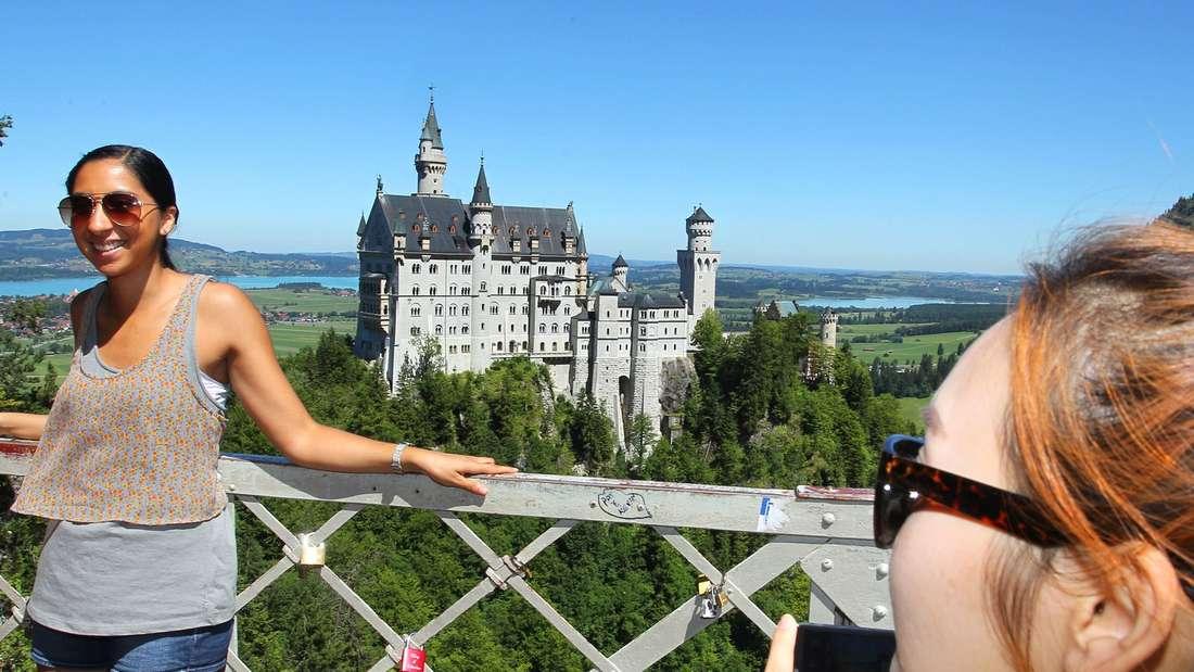 Touristen auf der Marienbrücke bei Hohenschwangau (Bayern) vor dem Schloss Neuschwanstein.