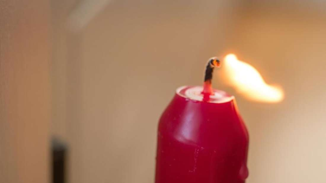 Mit einer brennenden Kerze kann man prüfen, ob die geschlossene Balkontür einen Luftzug durchlässt oder dicht ist.