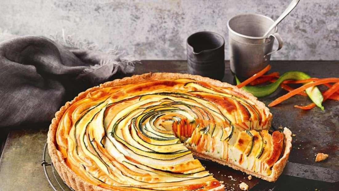 Die Gemüse-Spirale auf dem Tarteboden ist ein echter Hingucker. Für die Spirale werden die hauchdünnen Gemüsestreifen kreisförmig auf den Teig gestellt. Foto: Kramp + Gölling Fotodesign/Gräfe und Unzer/dpa-tmn