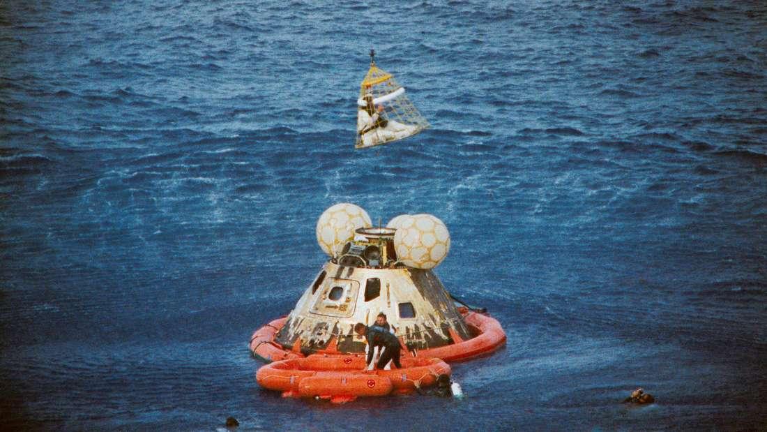 Rettung gelungen: Astronaut Jack Swigert wird aus dem Kommandomodul gehoben. Jim Lovell wartet noch auf seine Rettung, während Fred Haise bereits an Bord des Hubschraubers ist.