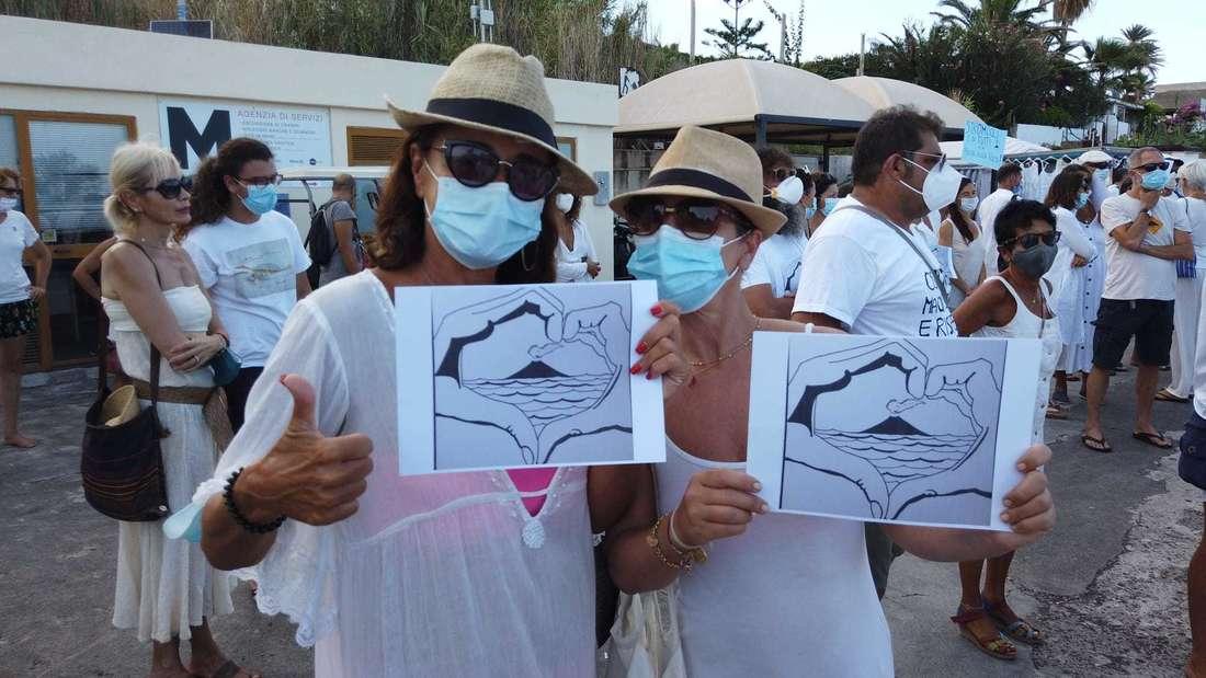 Stromboli: Demonstranten stehen mit Mundschutz und Protest-Transparenten auf der Uferpromenade. Um die Ausbreitung des Coronavirus zu verhindern, fordern Anwohner der kleinen italienischen Urlaubsinsel Stromboli eine Begrenzung des Tourismus.
