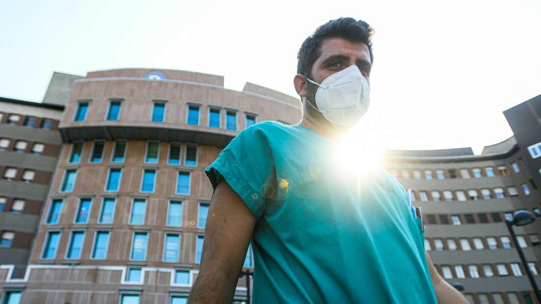 Ein medizinischer Mitarbeiter geht mit einer Maske außen am Mailänder Krankenhaus San Raffaele vorbei.