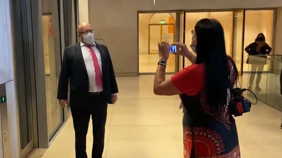 Peter Altmaier steht vor einem Aufzug im Bundestag. Eine Demonstrantin bedrängt und beschimpft ihn, während sie filmt.
