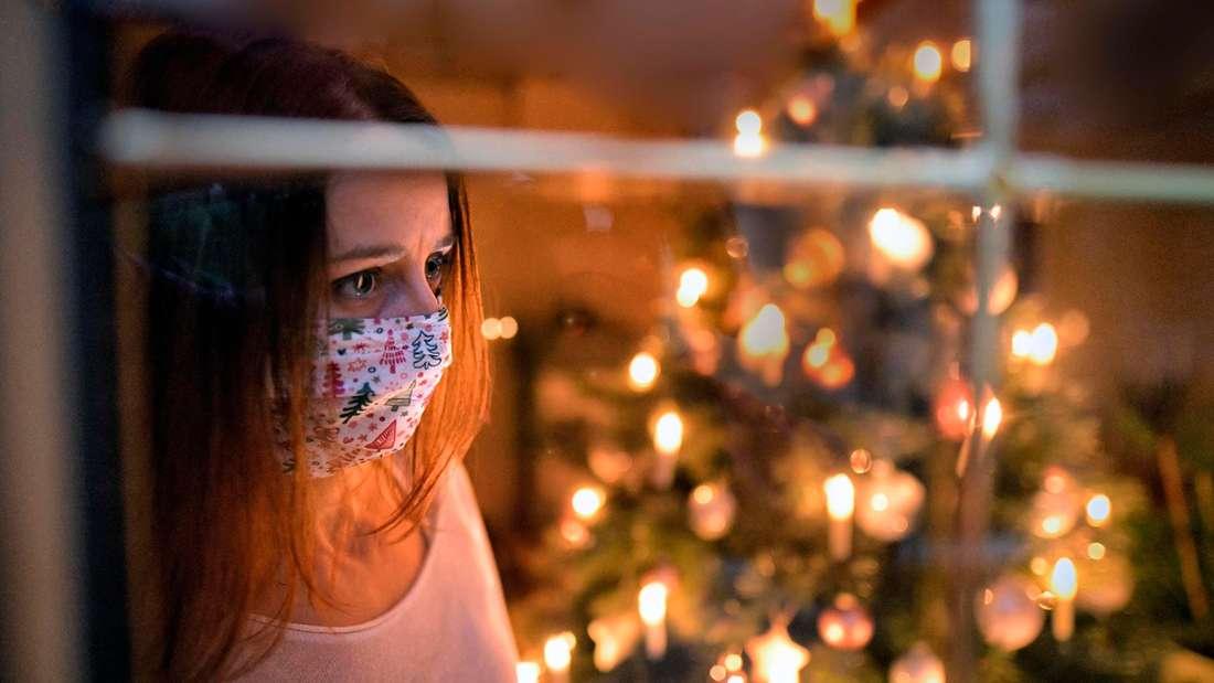 nachdenkliche Frau vor Weihnachtsbaum