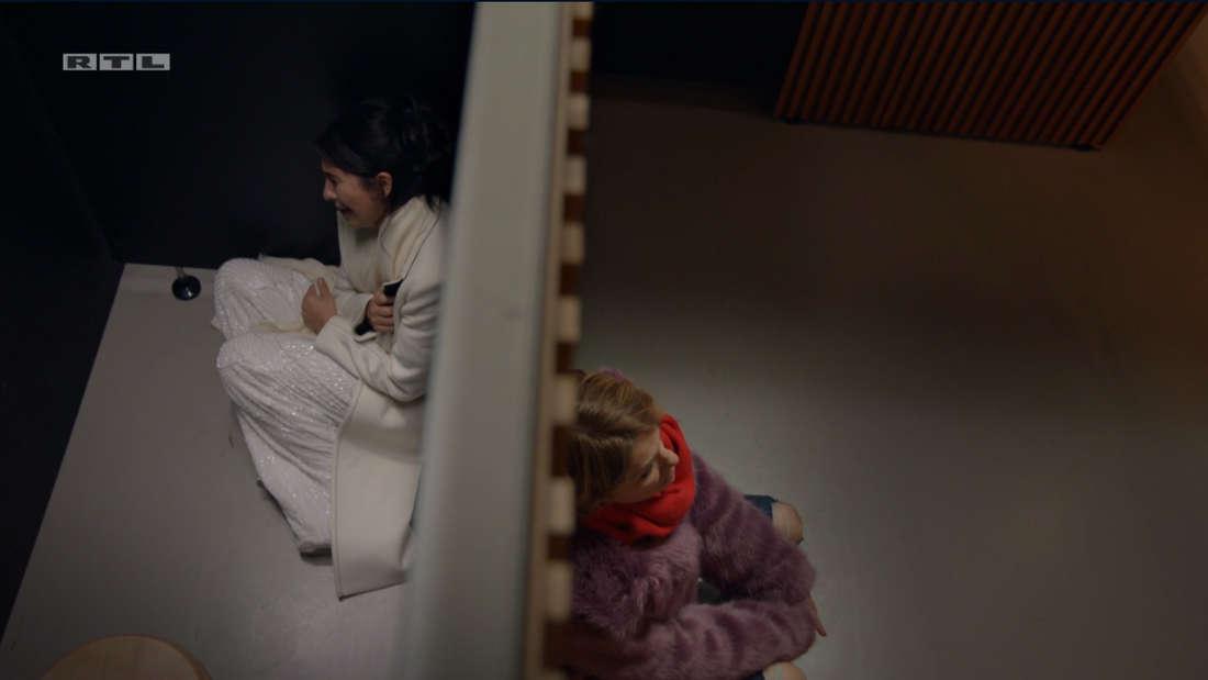 Aus der Vogelperspektive: Yvonne und Laura sitzen auf dem Boden, auf unterschiedlichen Seiten der Klo-Tür