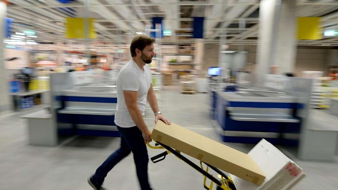 Ein Mann schiebt eine Sackkarre mit mehreren Kartons hinter dem Kassenbereich von Ikea entlang