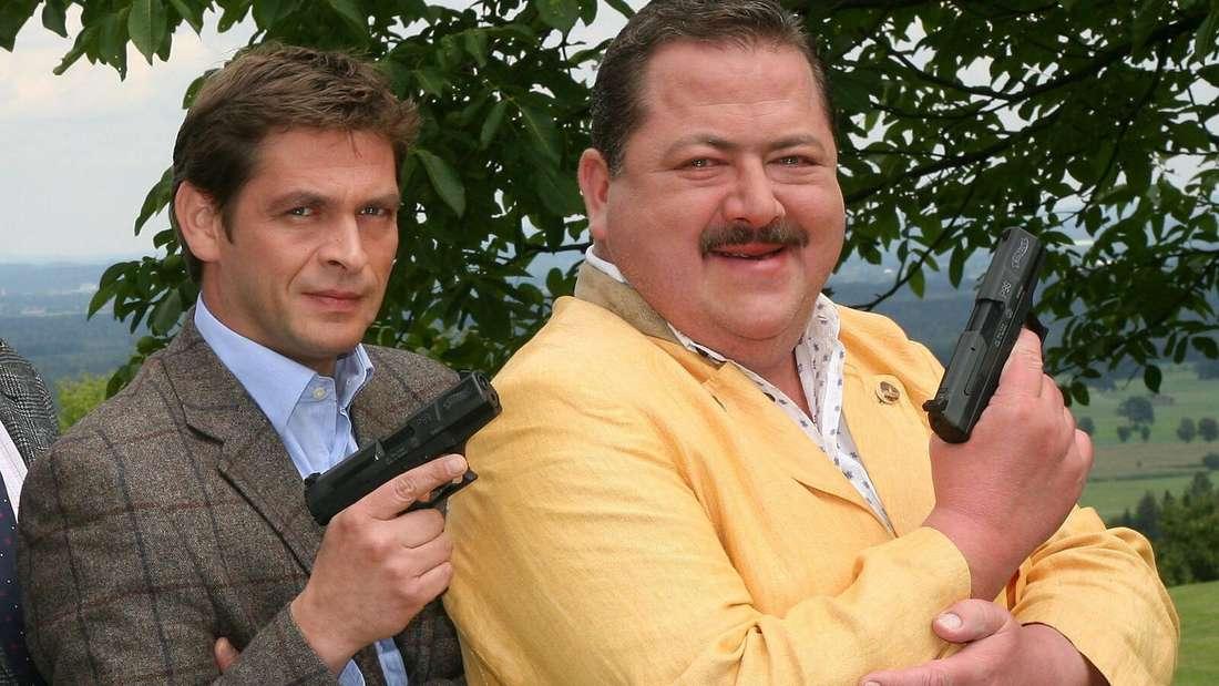 """Die Schauspieler und Fernsehkommissare Tom Mikulla und Joseph Hannesschläger zeigen während einer Pause bei Dreharbeiten für die ZDF-Serie """"Die Rosenheim-Cops"""" ihre """"Dienstwaffen"""""""