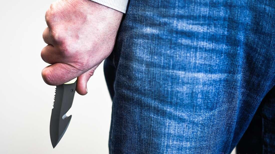 Ein Mann hält ein Messer in der Hand.