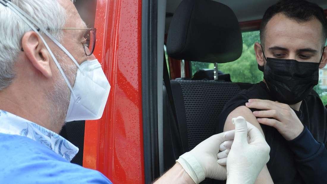 Ein Feuerwehrfahrzeug diente Dr. Friedemann Enders als mobile Impfstation. Auf dem Parkplatz an der Goethestraße impfte der Mediziner auch Mohammed Hami, der sich spontan bereit fand.