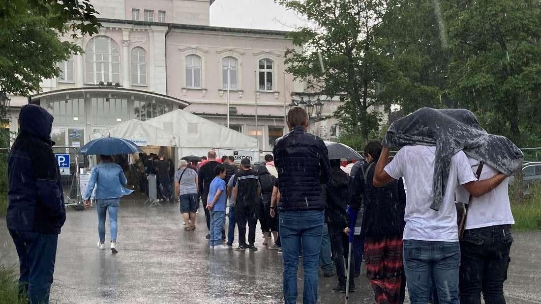 Der Regen prasselt um kurz nach 15 Uhr auf die Wartenden nieder. Vom Ende der Schlange bis ins Zelt dauert es anfangs knapp 45 Minuten.