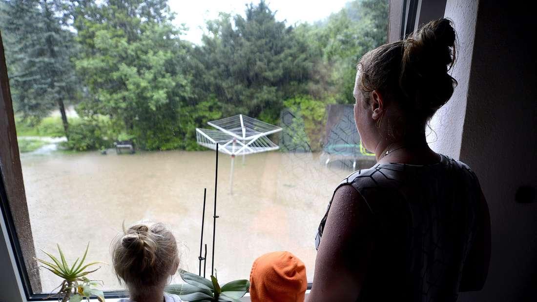 Frau mit Kindern am Fenster