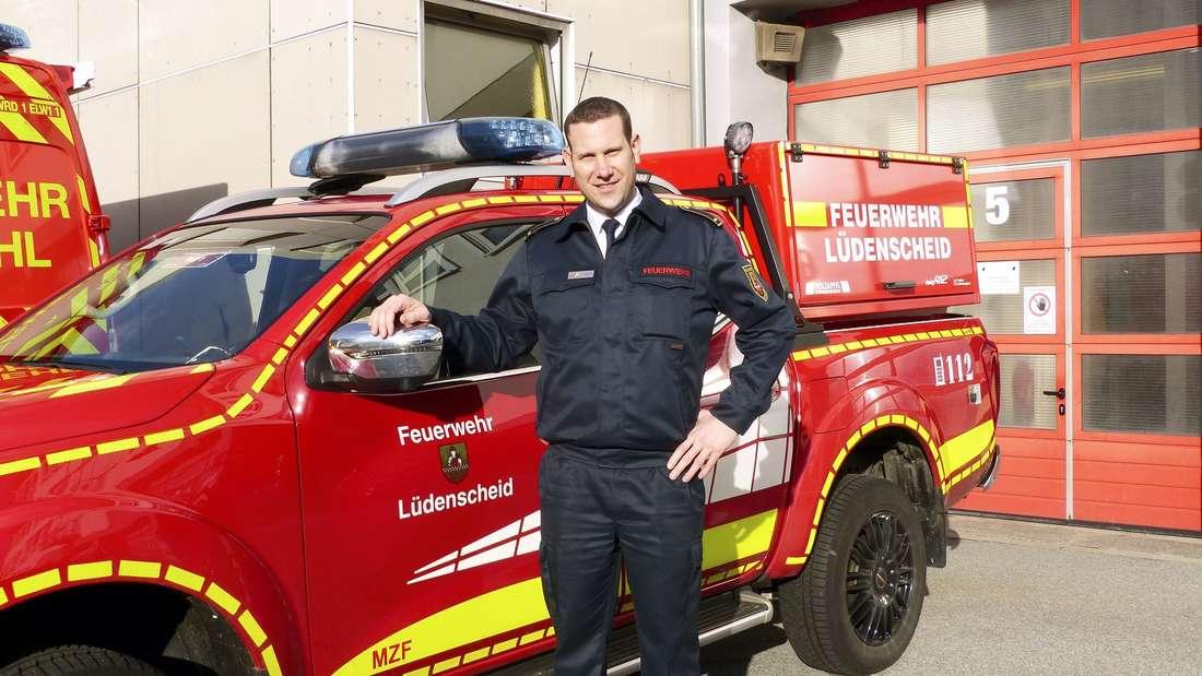 Feuerwehrmann vor Dienstwagen