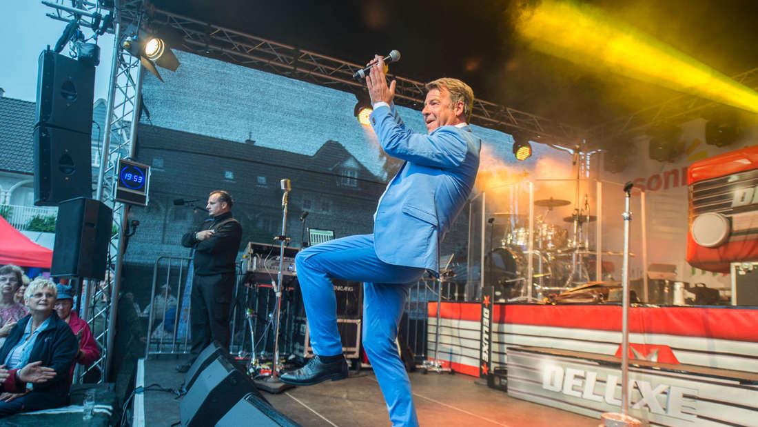 Patrick Lindner klatscht auf der Bühne in Essen und gibt ein Konzert im blauen Anzug