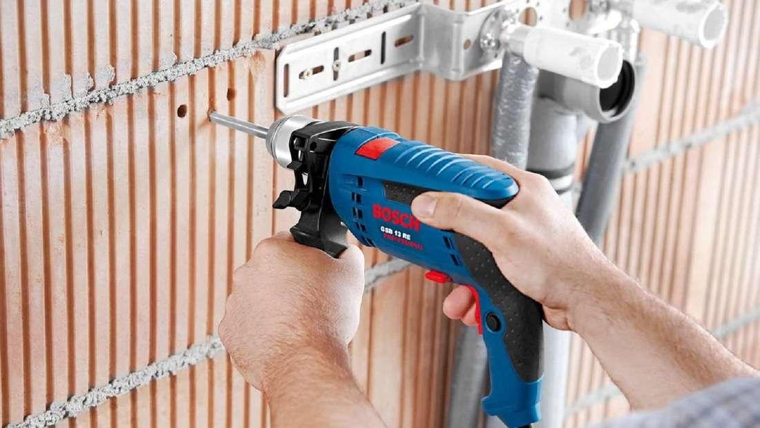 Mann arbeitet mit einer Bosch Schlagbohrmaschine am Mauerwerk.