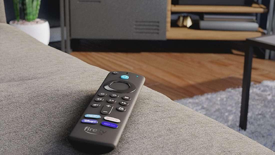 Der neue Fire TV Stick 4K Max liegt auf einer Couch, im Hintergrund läuft der Fernseher.
