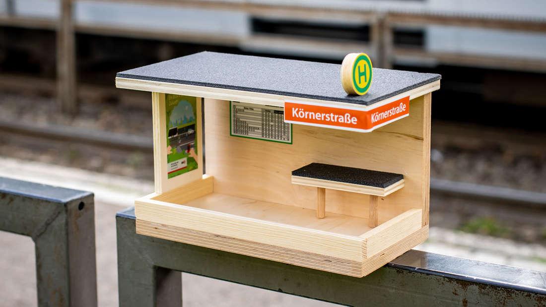 Das KVB-Vogelhäuschen im Look einer Haltestelle steht auf einem Geländer einer Bahnhaltestelle.